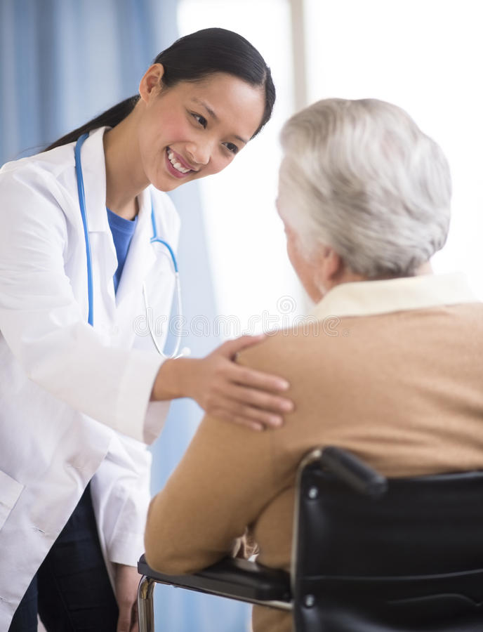 Doutor Consoling Senior Woman que senta-se na cadeira de rodas imagens de stock