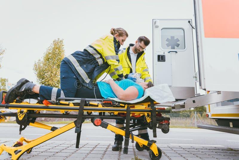 Doutor da emergência que toma da mulher seriamente ferida imagens de stock royalty free