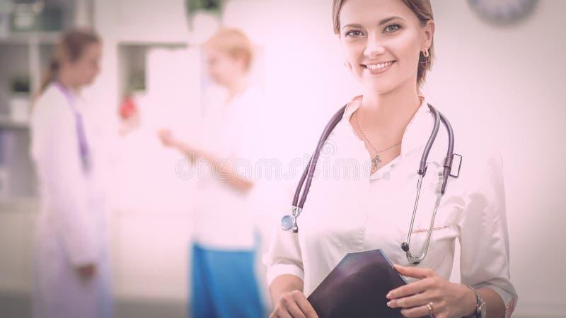 Doutor da jovem mulher que está no hospital com estetoscópio médico fotografia de stock