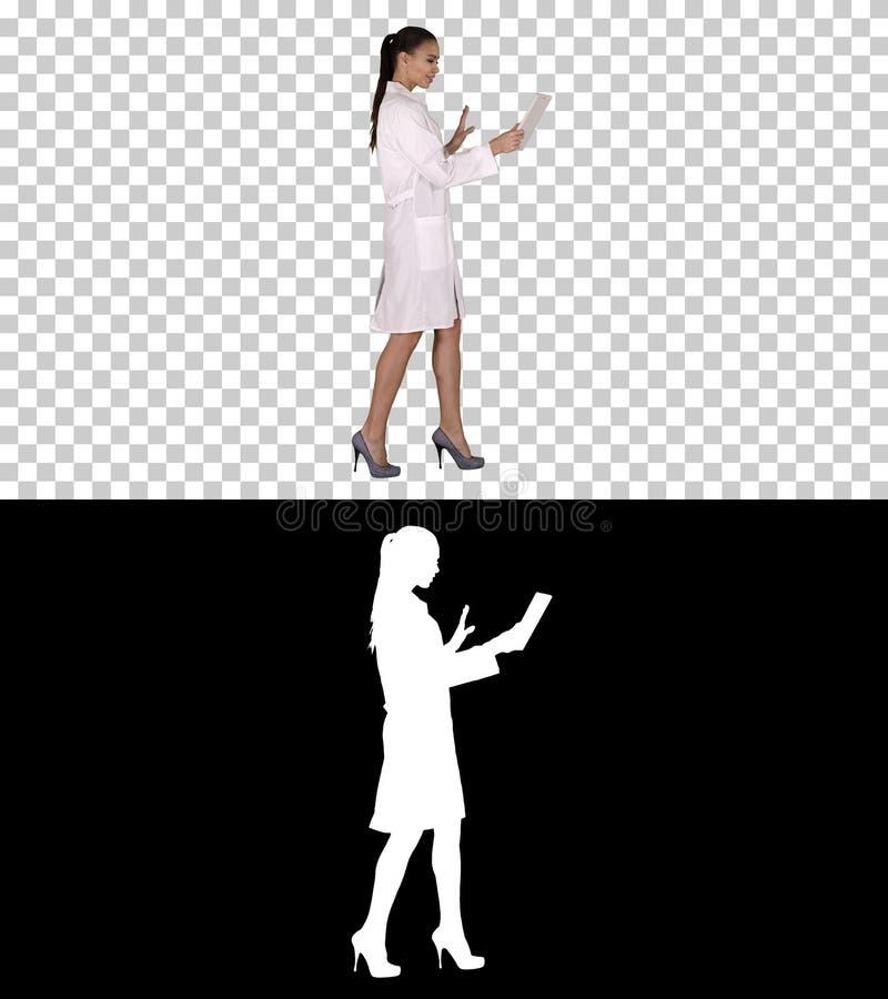 Doutor da jovem mulher que guarda a tabuleta em suas mãos e que faz a chamada video, Alpha Channel fotografia de stock
