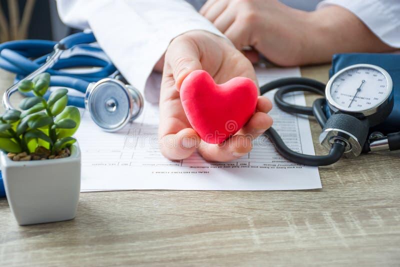 Doutor da medicina interna e cardiologista que realiza em suas mãos e mostras à figura paciente do coração do cartão vermelho dur fotografia de stock royalty free