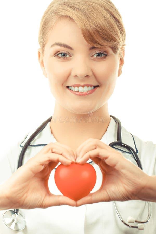 Doutor da mulher com o estetoscópio que guarda o coração vermelho, conceito dos cuidados médicos imagens de stock