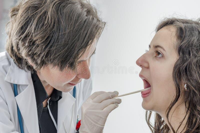 Doutor da mulher que usa um depressor de língua com paciente da menina imagem de stock royalty free