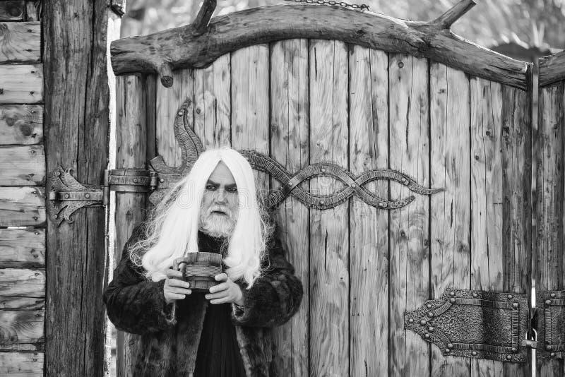 Doutor de bruxa idoso Homem farpado com caneca de madeira fotos de stock royalty free