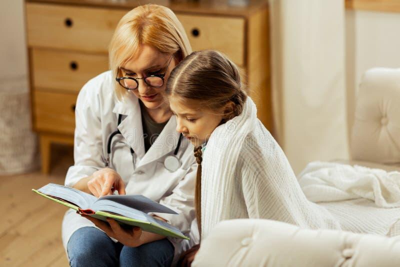 Doutor de encantamento que lê um livro com a menina doente bonito fotos de stock royalty free