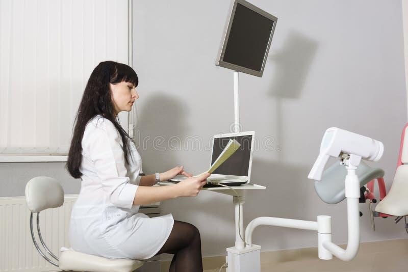 Doutor de meia idade em um revestimento branco que estuda os resultados do colposcopy Métodos do diagnóstico de doenças gynecolog foto de stock