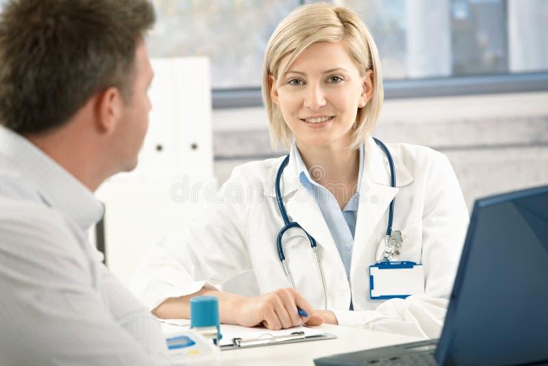 Doutor de sorriso com paciente foto de stock