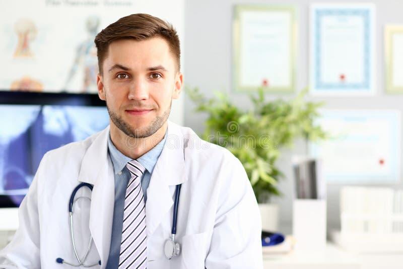 Doutor de sorriso considerável da medicina que senta-se no escritório imagem de stock royalty free