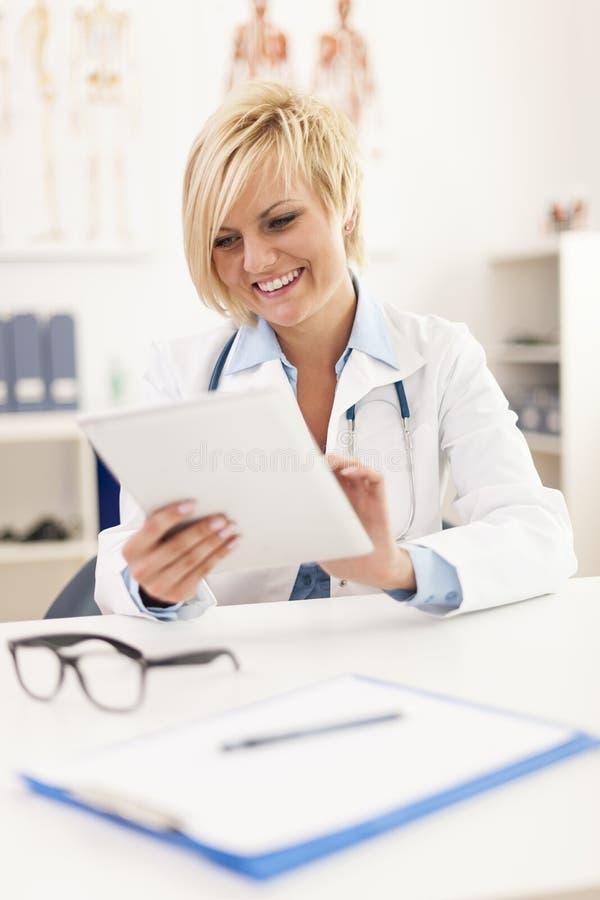 Doutor de sorriso em seu escritório fotos de stock royalty free