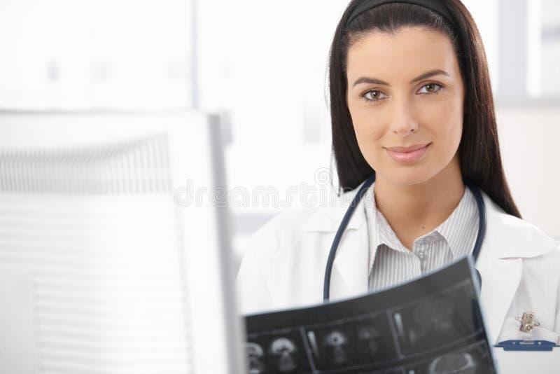 Doutor de sorriso ocupado com raio X imagem de stock