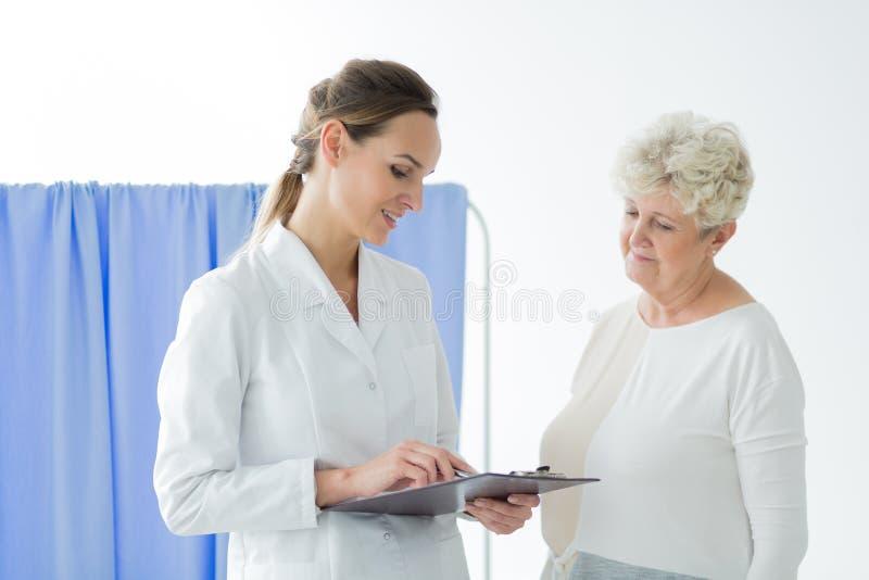 Doutor de sorriso que consulta resultados pacientes do ` s imagens de stock royalty free