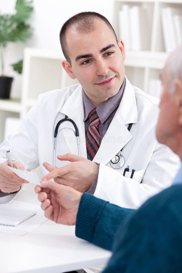 Doutor de sorriso que dá uma prescrição fotos de stock royalty free