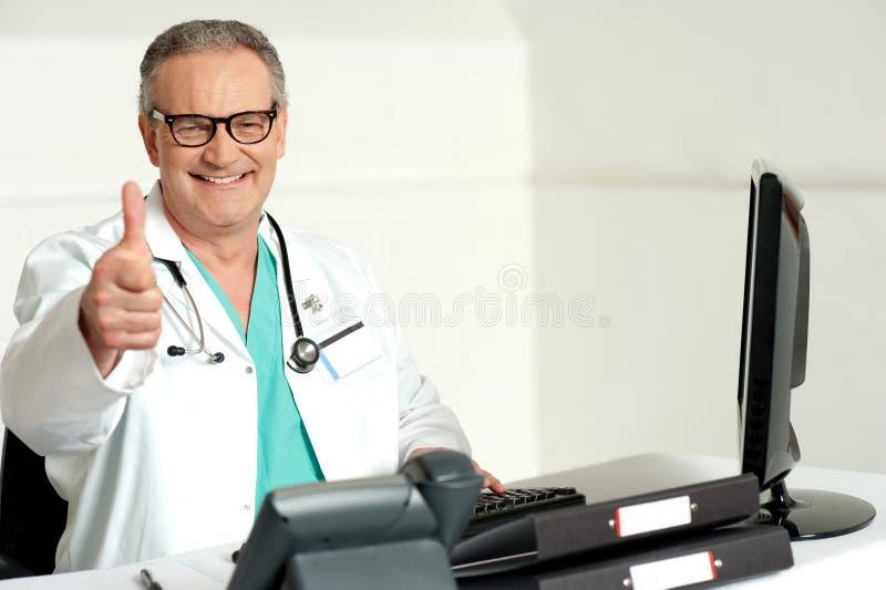 Doutor de sorriso que gesticula os polegares até a câmera fotos de stock royalty free