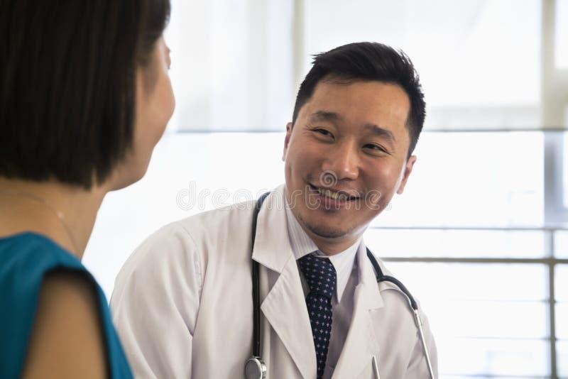 Doutor de sorriso que sentam-se para baixo e paciente de consulta no hospital, close-up imagens de stock royalty free