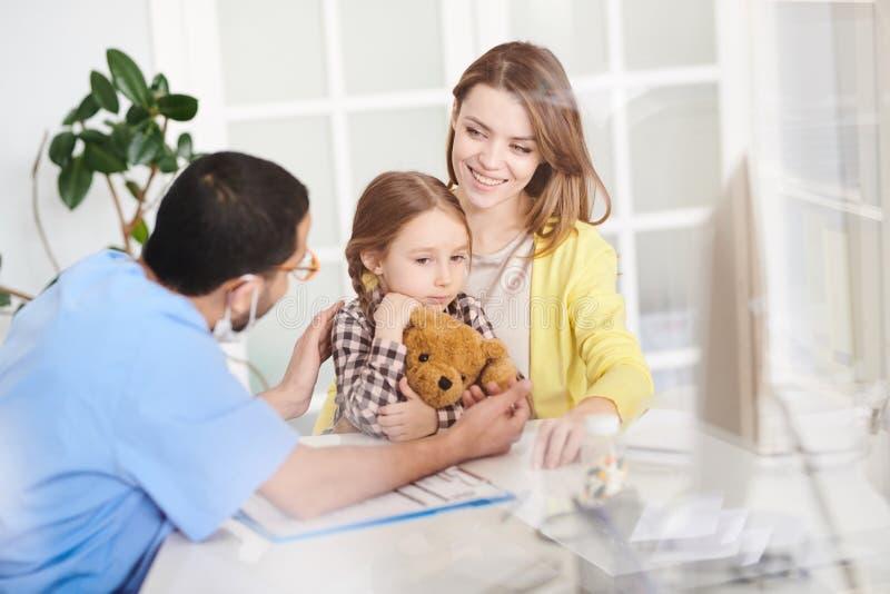 Doutor de visita da menina assustado imagem de stock royalty free