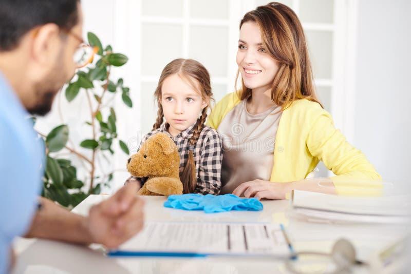 Doutor de visita da menina com mamã foto de stock