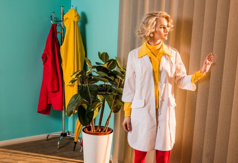 doutor denominado retro bonito no vestido colorido e no revestimento branco que olham através do jalousie fotos de stock royalty free
