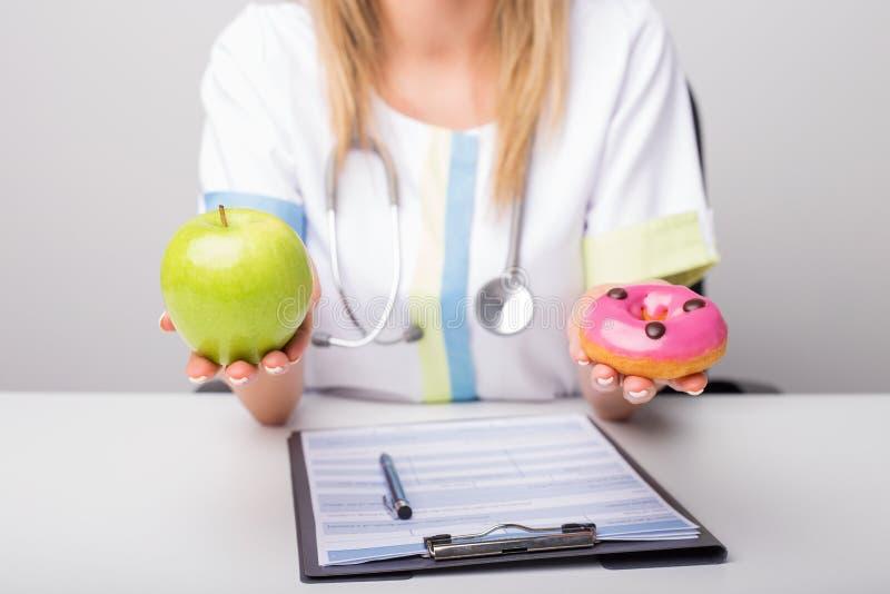 Doutor dietético que guarda anéis de espuma e maçã fotos de stock