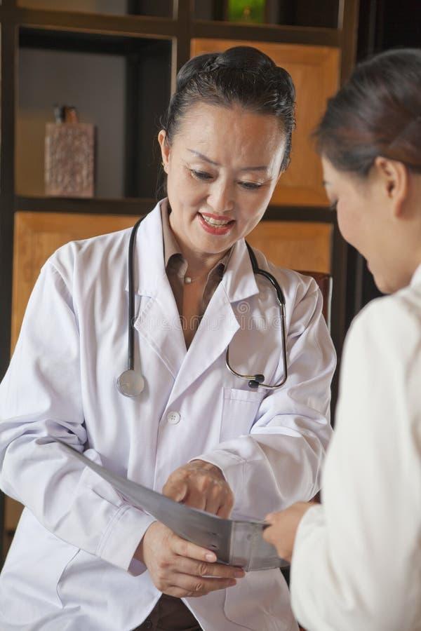 Doutor Discussing Medical Chart com enfermeira foto de stock