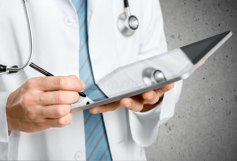 Doutor do close-up no hospital que trabalha com PC da tabuleta imagem de stock