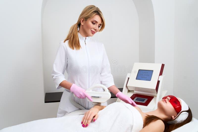 Doutor do esteticista que faz a depilação da remoção do cabelo dos elos nas mãos atrativas da jovem mulher no salão de beleza beu fotografia de stock