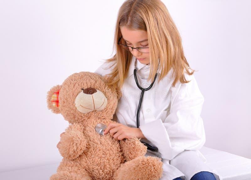 Doutor do jogo da menina com seu urso de peluche imagem de stock