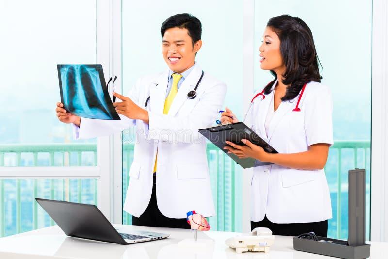 Doutor e enfermeira asiáticos na cirurgia fotos de stock royalty free