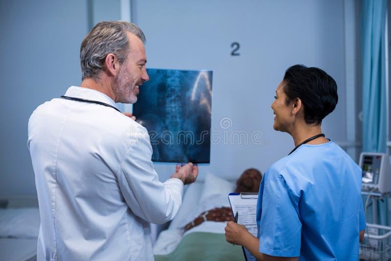 Doutor e enfermeira que discutem o raio X na divisão imagens de stock