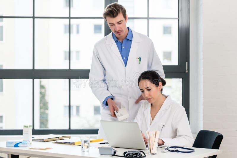 Doutor e farmacêutico que verificam a informação em um portátil em um hospital imagem de stock