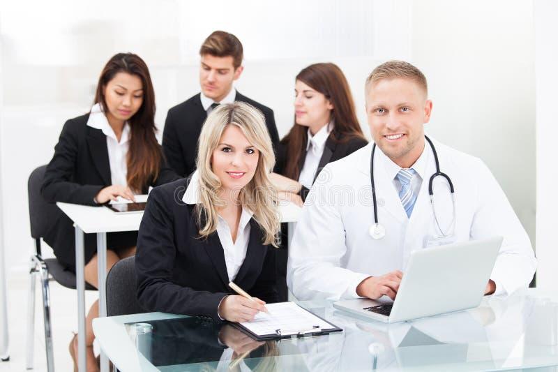 Doutor e mulher de negócios masculinos de sorriso com portátil foto de stock