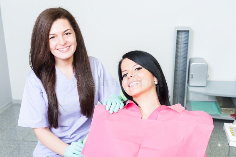Doutor e paciente fêmeas amigáveis e bem sucedidos do dentista imagem de stock