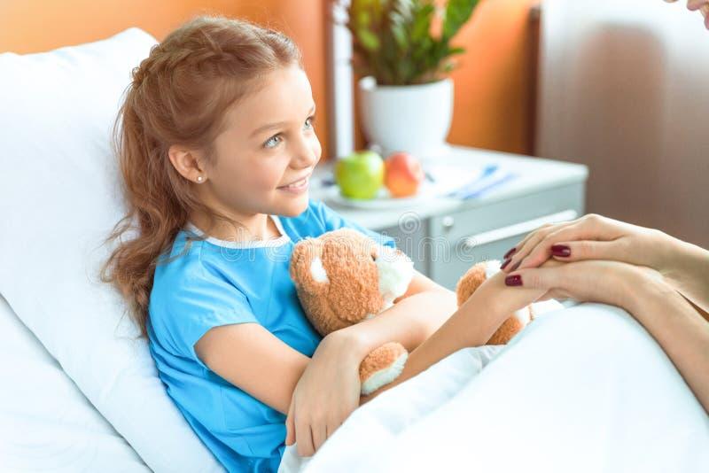 Doutor e paciente pequeno com o urso de peluche que guarda as mãos fotografia de stock royalty free