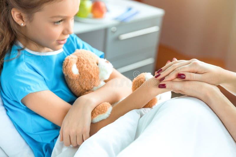 Doutor e paciente pequeno com o urso de peluche que guarda as mãos no hospital fotografia de stock royalty free