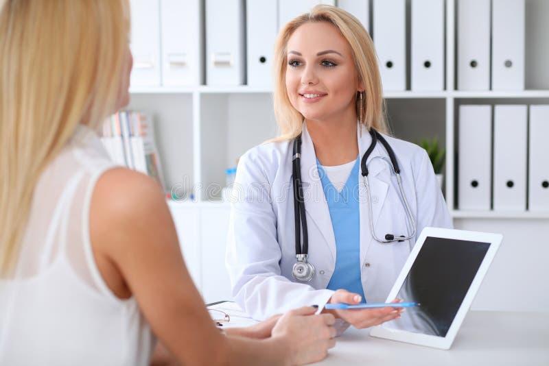 Doutor e paciente que discutem algo ao sentar-se na tabela no hospital Médico que usa o PC da tabuleta para fotografia de stock