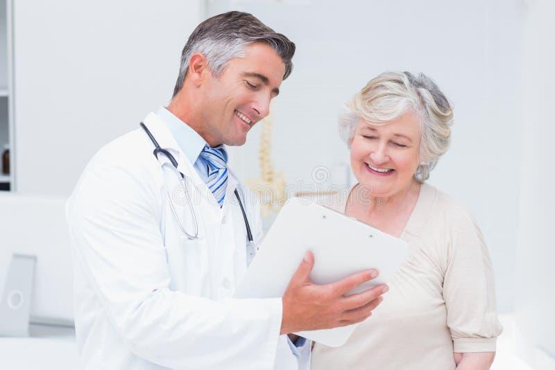 Doutor e paciente que discutem sobre relatórios imagens de stock