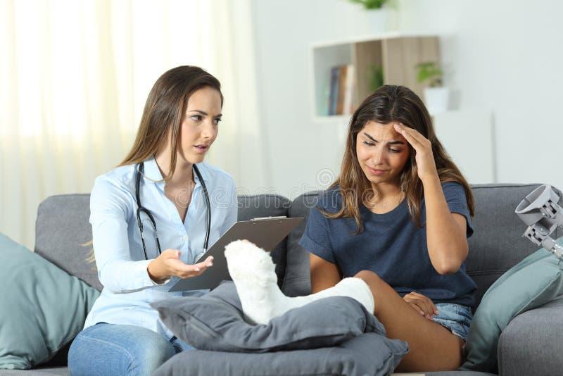 Doutor e paciente triste com pé do emplastro fotos de stock