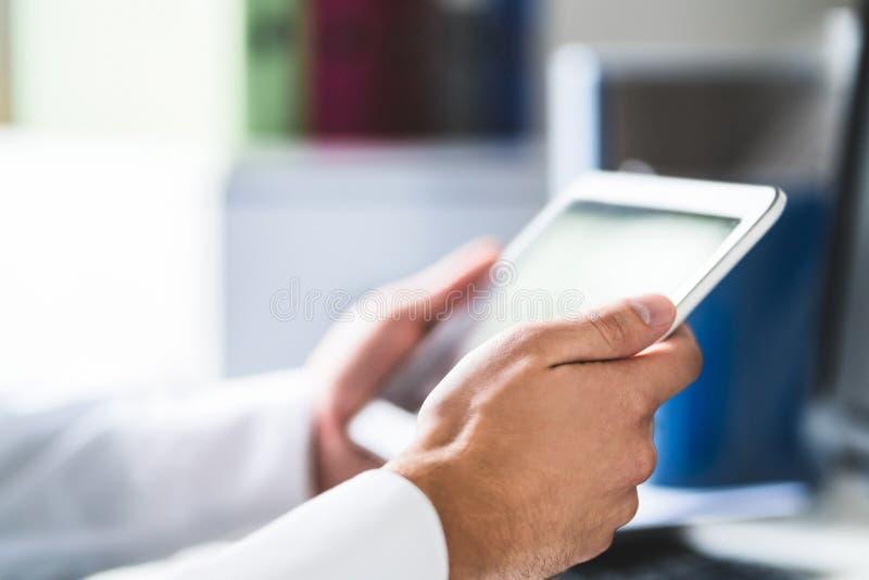 Doutor e profissional médico que usa a tabuleta no trabalho nos cuidados médicos foto de stock royalty free