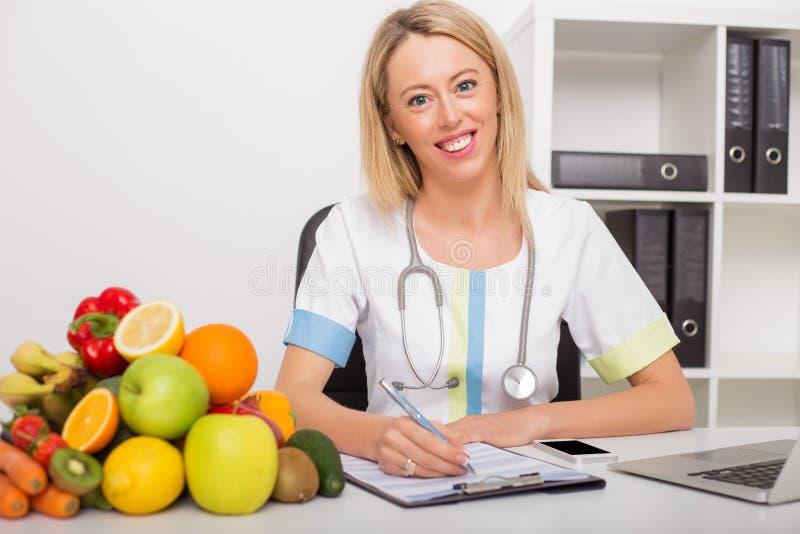 Doutor em seu escritório com vegetais e frutos foto de stock