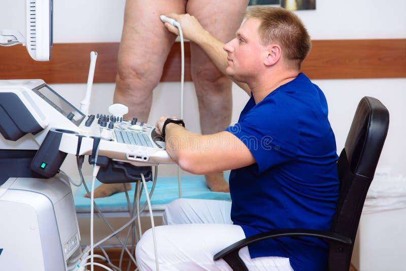 Doutor em um revestimento azul com uma clínica com equipamento diagnóstico O homem do cirurgião executa um ultrassom usando um di foto de stock