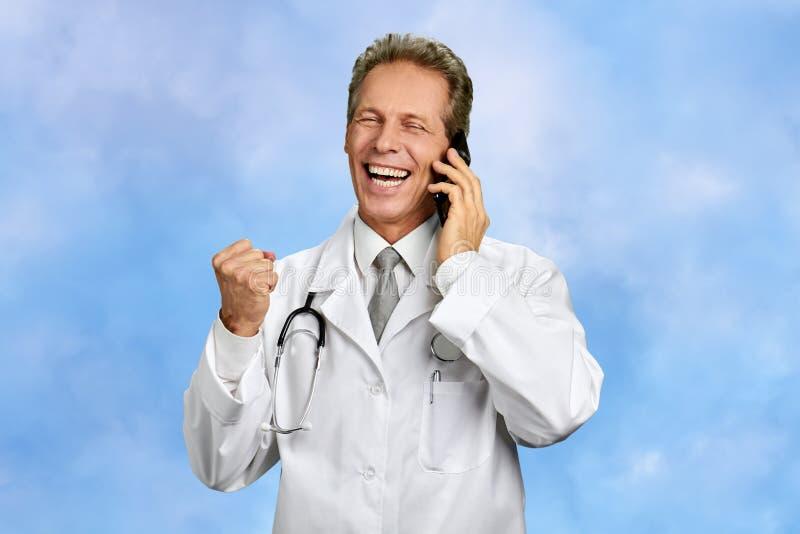 Doutor entusiasmado que fala no telefone celular imagem de stock