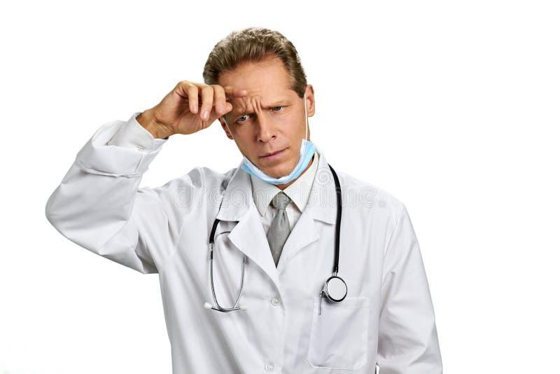Doutor envelhecido meio que olha incomodado fotografia de stock