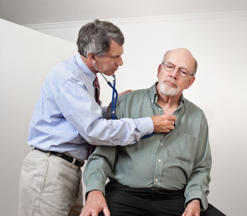 Doutor Escuta o coração de homem mais idoso fotografia de stock royalty free