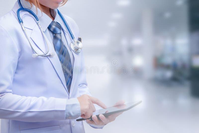 Doutor esperto da mulher que guarda a tabuleta e que aponta à tela foto de stock royalty free
