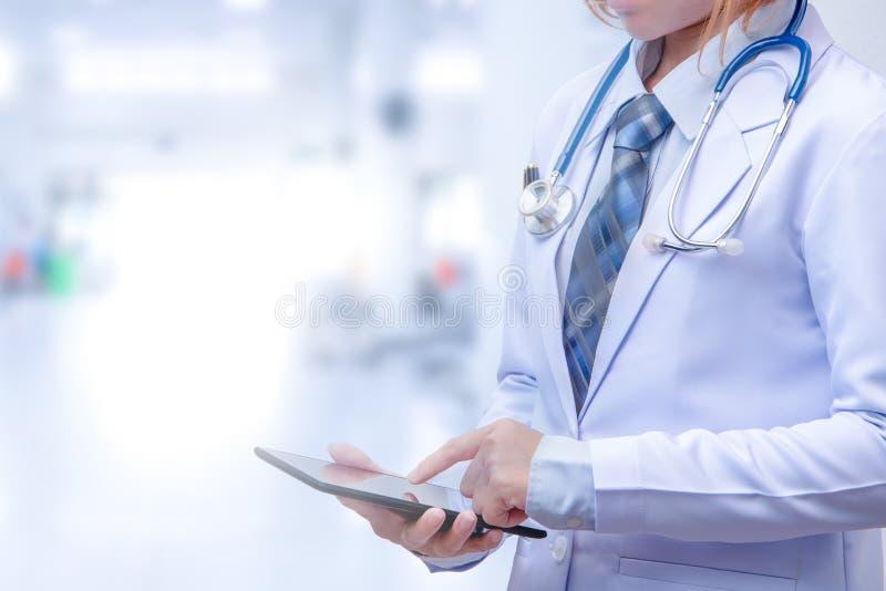 Doutor esperto da mulher que guarda a tabuleta e que aponta à tela fotos de stock royalty free