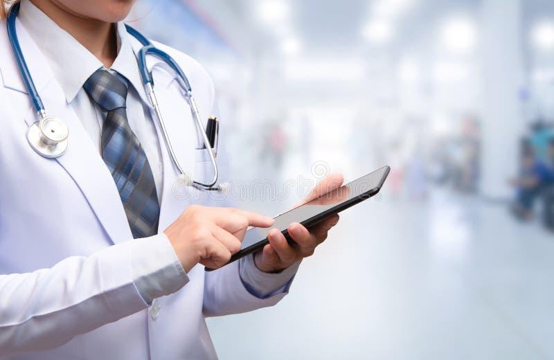 Doutor esperto da mulher que guarda a tabuleta e que aponta à tela fotografia de stock royalty free