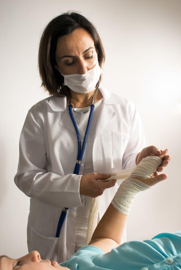 Doutor Exame um braço enfaixado. Vertical fotos de stock