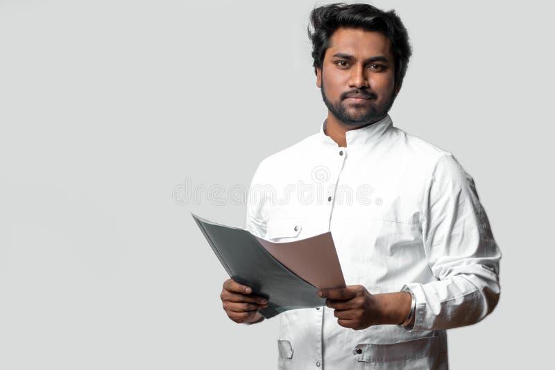 Doutor experiente da Índia que guarda o dobrador e os originais fotografia de stock
