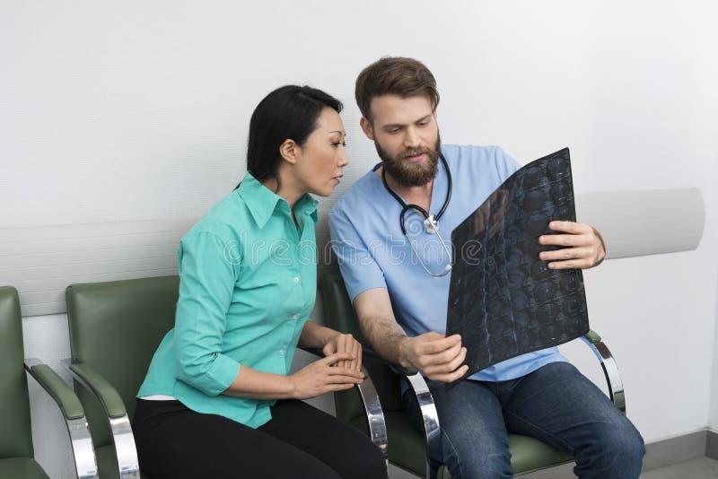 Doutor Explaining Raio X Paciente na entrada do hospital fotografia de stock