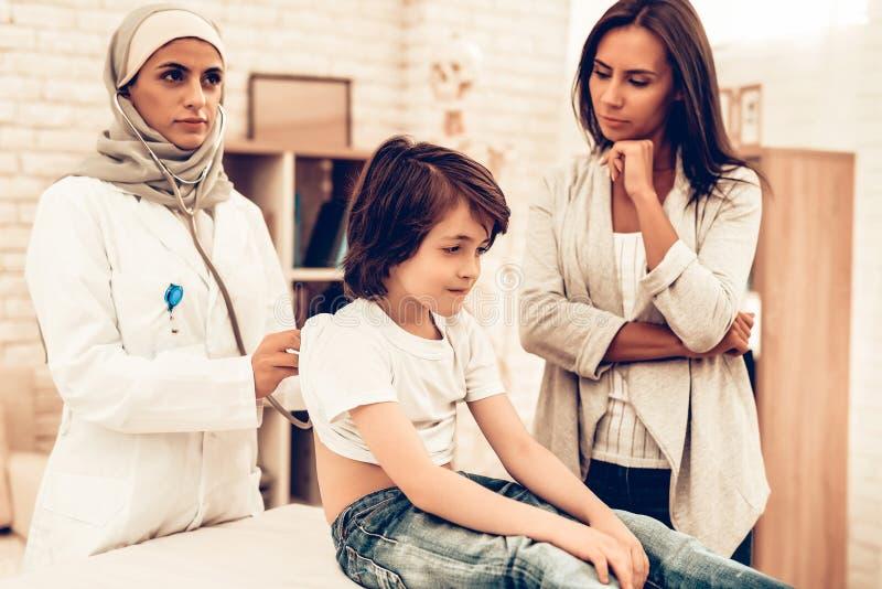 Doutor fêmea árabe Examining Little Boy foto de stock