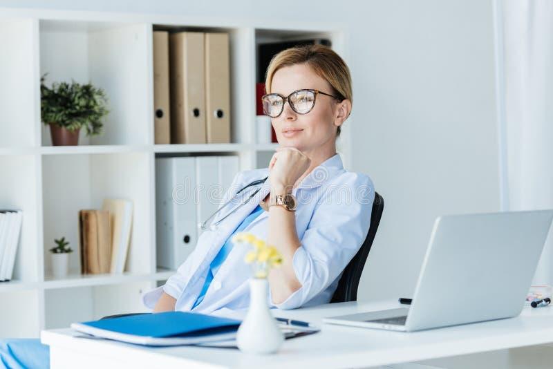 doutor fêmea adulto pensativo nos monóculos que sentam-se na tabela com portátil fotografia de stock royalty free